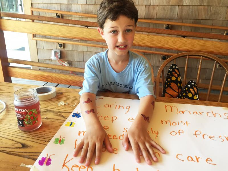 Erik Kowalski, 8, shows off his fake tattoos of monarch butterflies at the workshop