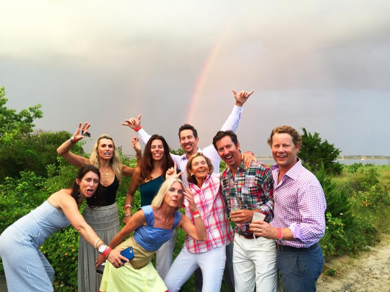 Guests pose for photos in front of the rainbow after the storm passed