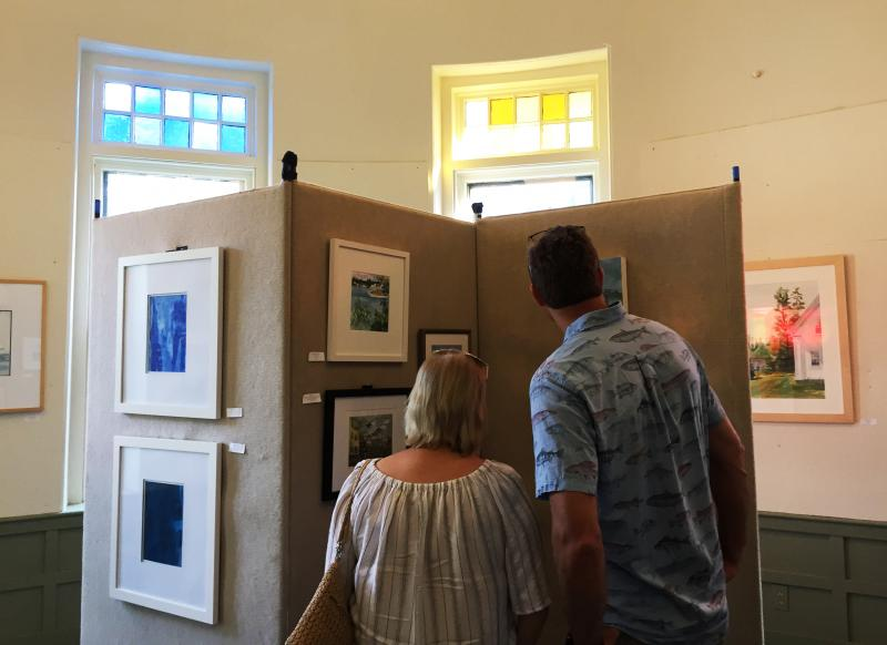 Visitors admire the artwork at the Art Drive preview exhibit in the Olde Southworth Library
