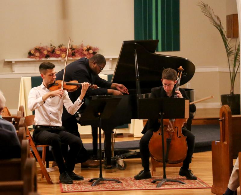 Chase Ward, Evan Hines, and Sophie Applbaum performing Claire Cowan's 2008 piece called wood:strings:hammers:flesh at the concert