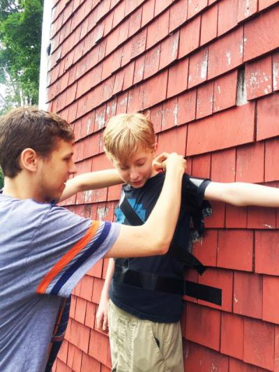 Kenny, 19, tapes his 13-year-old brother Ben to the wall of a barn