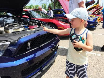Max Moniz, 4, holds a toy Miatta while pointing out his favorite car