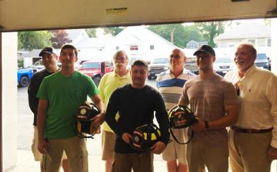 The graduated firefighters show off their new black helmets while the Prudential Committee looks on