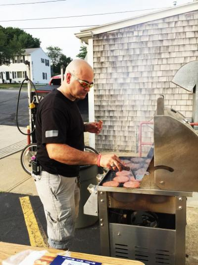 Department member Charlie Silvia grills some meat for the cookout