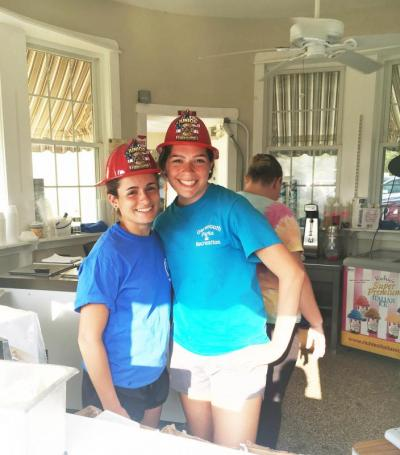 Bucket workers Ally Amaral and Merideth Nailor wearing plastic firefighter helmets for the occasion