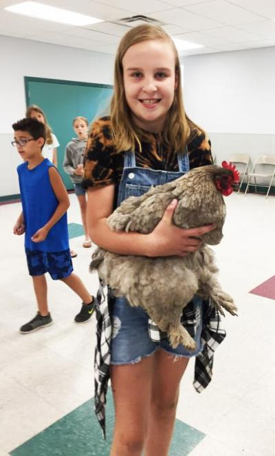 Addison Thompson, 10, holds her favorite hen, Country, a cochin chicken with feathered legs