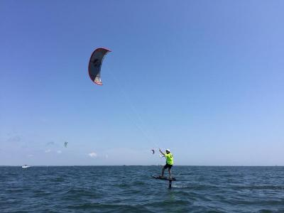A kiteboarder rides on his foil during a practice run before the start of the race
