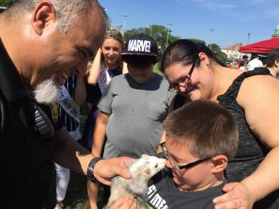 Gage Kendrick, 9, gets a nuzzle from Slinky the ferret while his mother and Maciel look on.