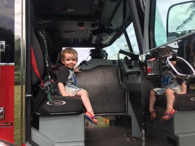 Meanwhile Sophia's brother Teddy, 2, perches happily inside the fire truck.