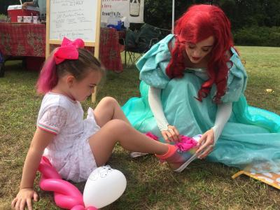 Princess Ariel not only played drums and signed autographs — she also helped Savannah Woodcock, 6, with her shoes.