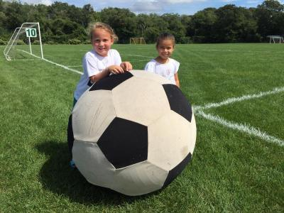 Regan Wilson and Averie DaCosta, both 5, play with a giant soccer ball.