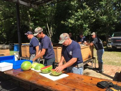 Firefighters cutting up some watermelon for dessert.
