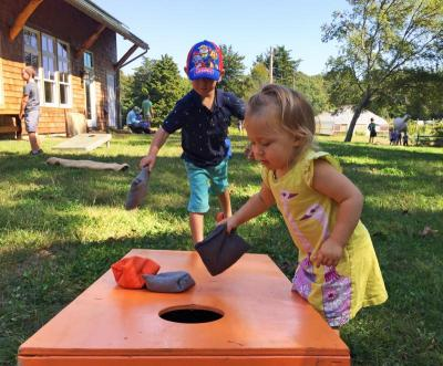Calum, 4, and Scarlett Walker, 1, play their own version of corn hole.