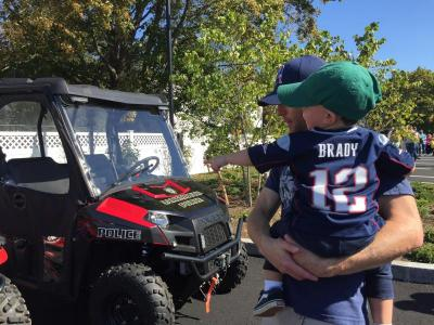 Teddy Taylor, 2, in his Patriots jersey points out his favorite police vehicle to dad Ben while they wait for the station tour.