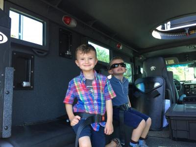 Aidan Levesque, 4, explores the inside of the S.W.A.T. van with his friend Gabriel Kelley, 4, of Melrose.