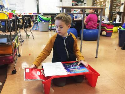 Tyler Calvao, 8, uses a sitting desk.