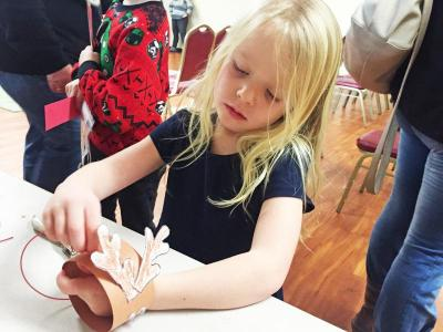 Dartmouth, MA news - Christmas at Southworth Library - Charlotte Flannery, 4, puts the finishing touches on her reindeer ornament.