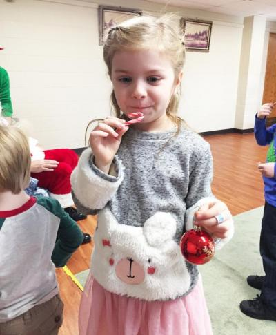 Dartmouth, MA news - Christmas at Southworth Library - Six-year-old Adriana Debarros munches on a candy cane while decorating the tree.