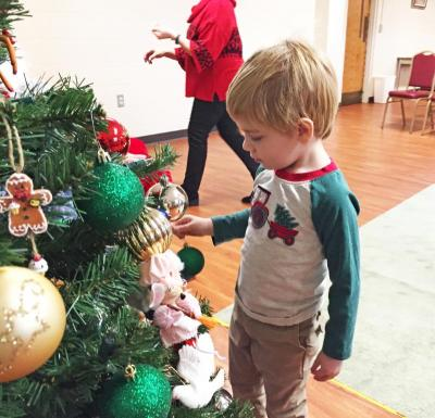 Dartmouth, MA news - Christmas at Southworth Library - Three-year-old Luke Debarros of Dartmouth decorates the tree. He asked Santa for an orange and blue guitar for Christmas.
