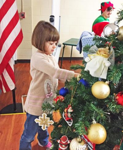 Dartmouth, MA news - Christmas at Southworth Library - Acushnet resident Victoria Martins, 4, decorates the tree.