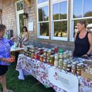 Carrie Richter from PeachTree Circle Farm in Falmouth speaks with a customer about her pickled goods. Richter brought several varieties of garlic to the party.