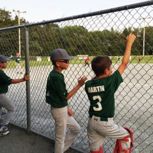 The Dartmouth 9 and under team watch from the dugout at the John B. Steele tournament on Friday evening