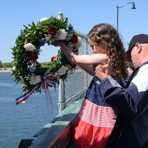 Dartmouth Week - Dartmouth, MA news - Lauren Rose-Wells and her grandfather, Norman Giovannini conduct the wreath throwing ceremony on the Padanaram Bridge. Photo by: Douglas McCulloch